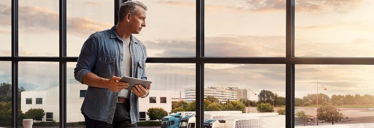 Moški, ki drži tablični računalnik, stoji ob oknu in gleda svoj vozni park
